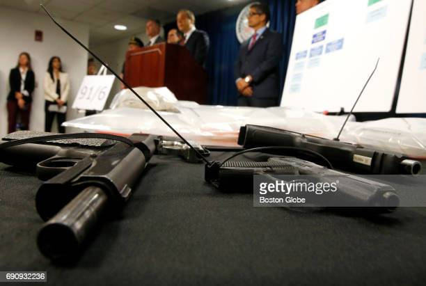 Confiscated firearms are seen in the foreground as Acting United States Attorney William D Weinreb announces federal drug firearm and immigration...