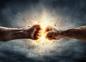 Two Fiery Fists In Impact With Stormy Sky In Background