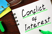 Conflict of interest sign written in a notepad.