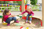 Conflict on the playground. Two kids fighting over a toy shovel in the sandbox