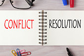 Conflict vs Resolution written on notebook with marker pen. Business Concept.