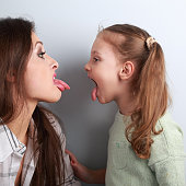 Conflicting funny mother and daughter disputing and showing each other the tongues. Closeup portrait