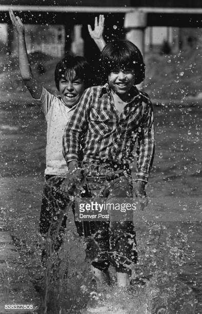 Confluence park Front Albert Guzman age 11 in Back Raul Sanchez age 10 They are playing in the water of the plate river running along the dock area...