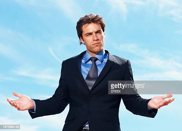 Confused and puzzled young business man against sky