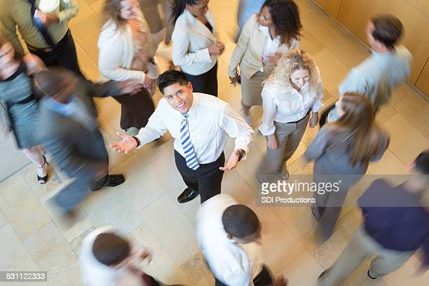 Confused Asian businessman lost in busy crowd of professionals