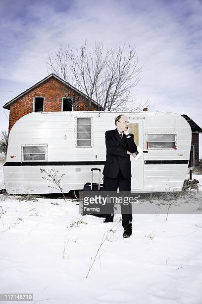 Confused business traveler outside an abandoned trailer and house
