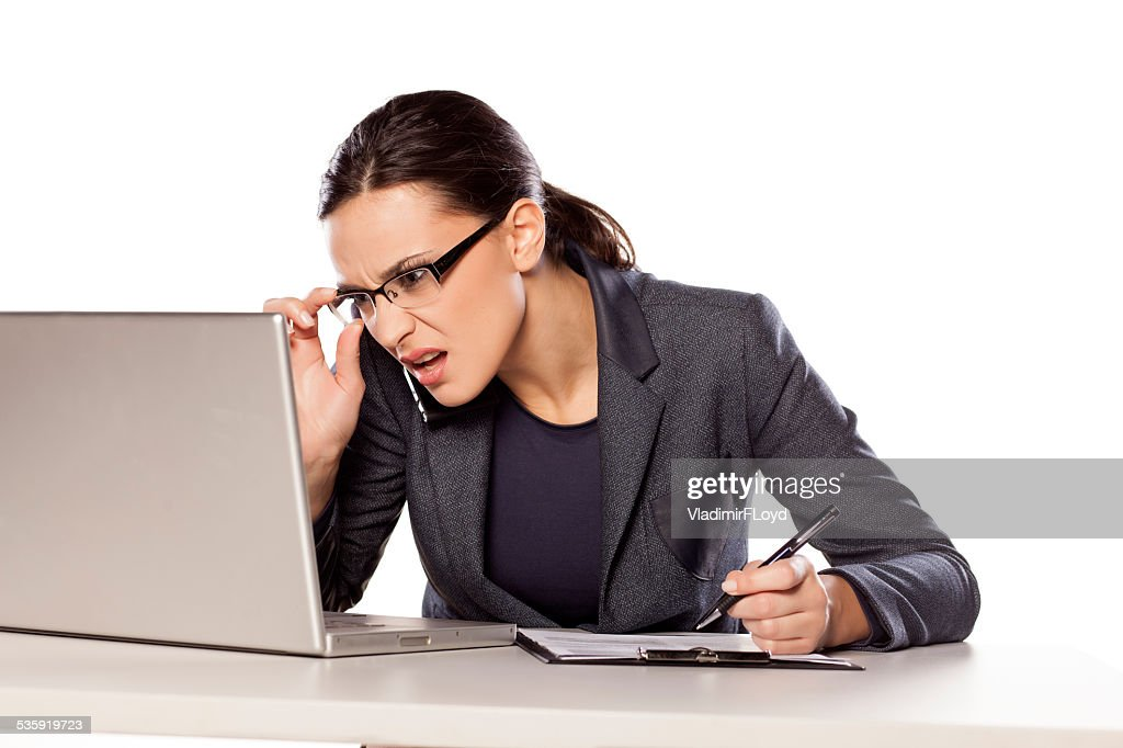 Confused business woman working on a laptop and writing : Stock Photo