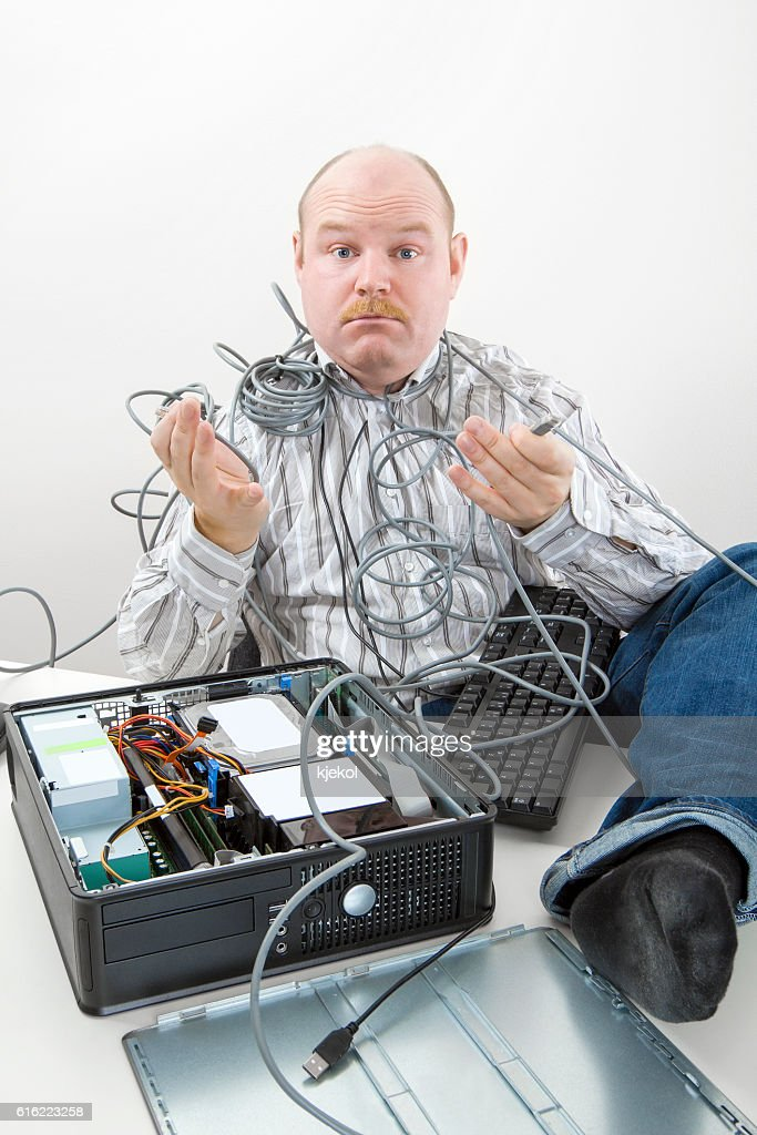 Confused Businessman Holding Tangled Cables Of Computer At Desk : ストックフォト