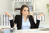 Front view portrait of a confused businesswoman shrugging shoulders looking at camera at office