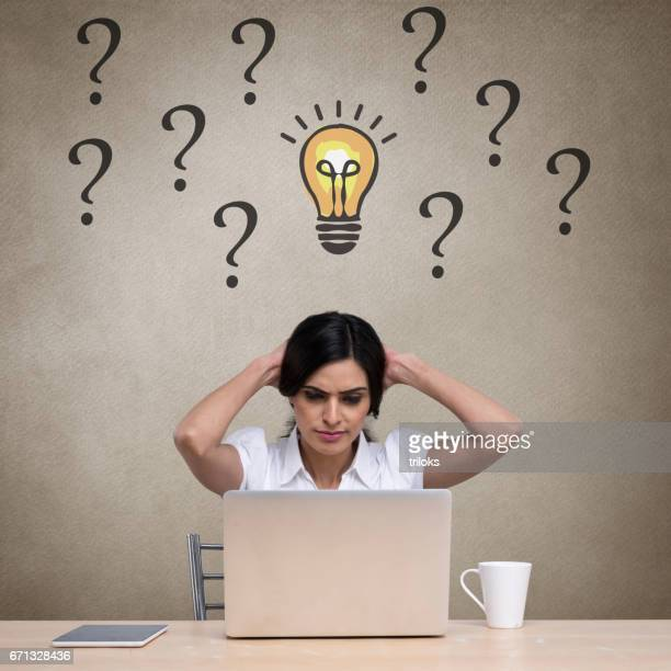 Confused businesswoman working on laptop