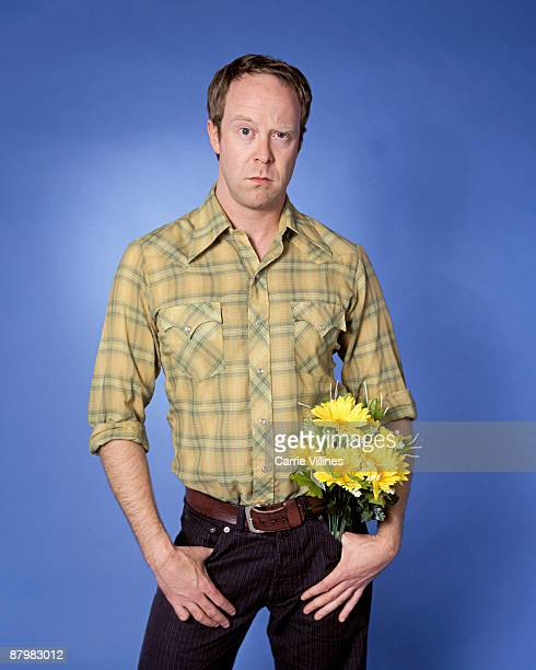 Confused man with bouquet of flowers