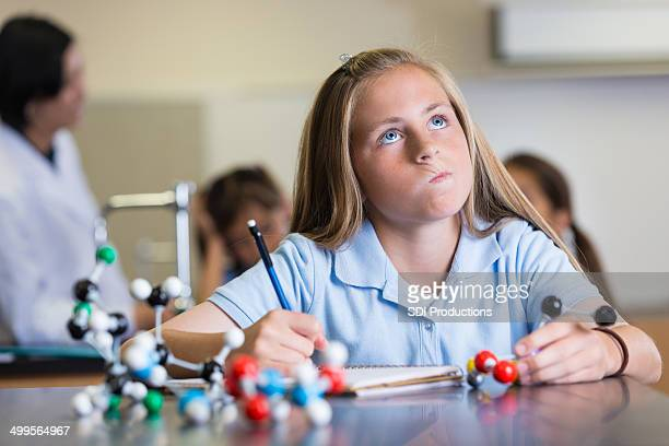 Confused preteen student using atom model during exam in class
