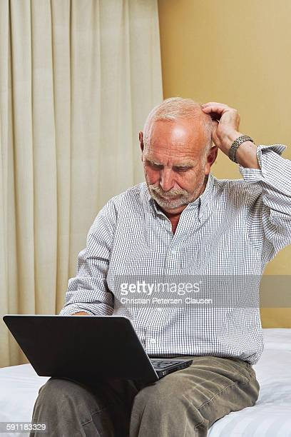 Confused senior trying to use laptop