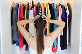 Back view of caucasian woman frustrated in front of a wardrobe