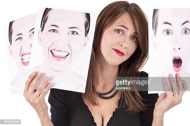 Confundida mujer agarrando fotografías de sus emociones