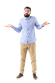 Confused young bearded businessman shrugging shoulders looking at camera. Full body length portrait isolated on white studio background.