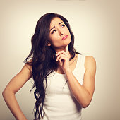 Confusion grimacing brunette woman thinking and looking up in white t-shirt. Toned closeup portrait