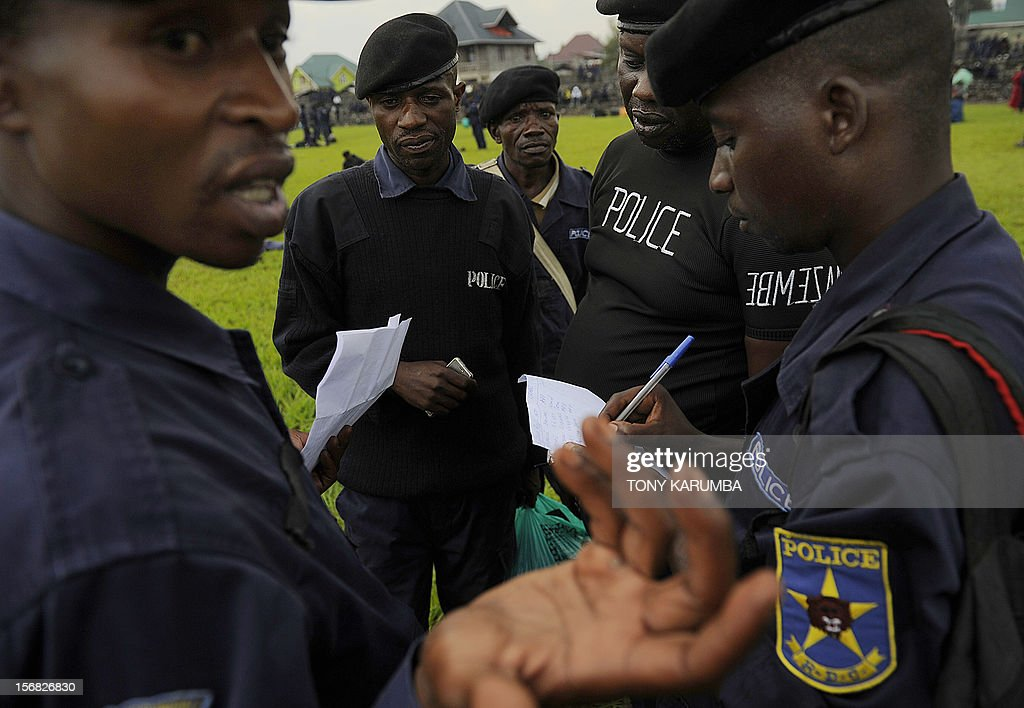 DR Congo police officers participate in a registration excercise on November 22, 2012 carried out by rebel group M23 at the Goma stadium. The M23 called on members of the Congo police and military to register for re-training by its troops which is meant to integrate them into the rebel movement's new style of leadership even as the rebels rejected international calls to pull out of the strategic eastern city of Goma, demanding peace talks with President Joseph Kabila before ending an offensive that has stoked fears of a wider conflict and humanitarian catastrophe. The political leader of the M23 rebel group in the Democratic Republic of Congo, Jean-Marie Runiga Lugerero headed to Uganda on Thursday for talks with President Yoweri Museveni, currently the Chief of the International Conference on the Great Lakes Region. AFP PHOTO/Tony KARUMBA