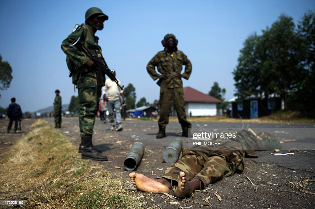 Congolese Army soldiers stand over the body of an alleged M23 fighter in Kanyarucinya, some 12 kms from Goma, in the east of the Democratic Republic of the Congo on July 16, 2013. The army in the Democratic Republic of Congo on July 16 pursued an offensive against rebels of the M23 movement to protect the North Kivu provincial capital of Goma. M23, a movement launched by Tutsi defectors from the army who accuse the Kinshasa government of reneging on a 2009 peace deal, last year occupied Goma for 10 days before pulling out under international pressure. AFP PHOTO / PHIL MOORE