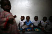Congolese child refugees some orphaned or separated from their family after conflict in the region displaced them eat as they find shelter at the Don...