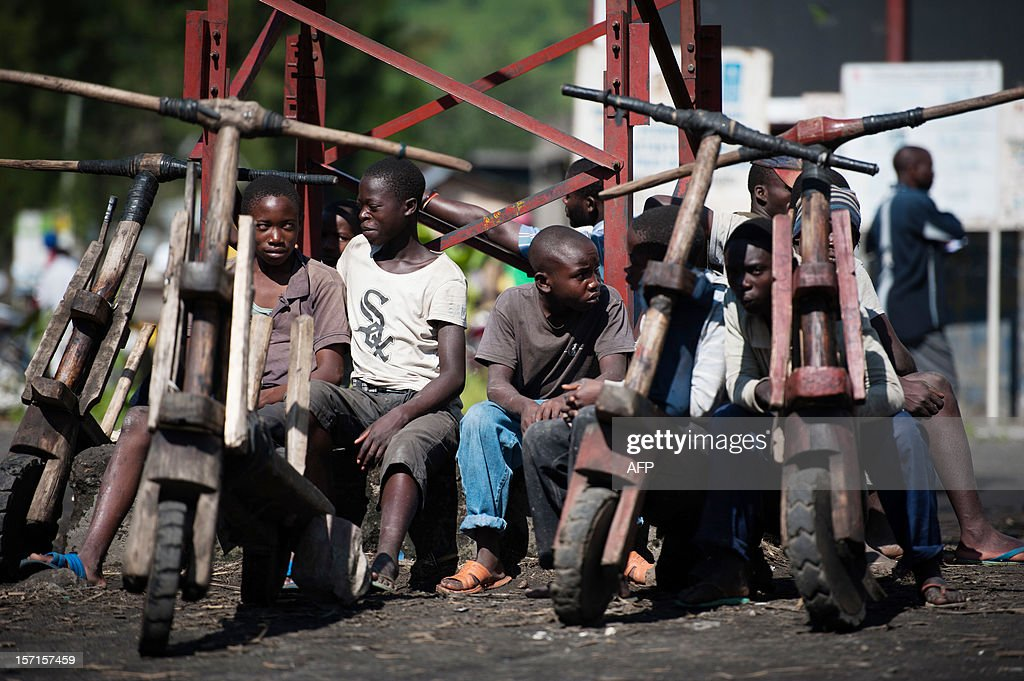 Congolese children sit next to their 'chukudus', wooden bicycles specific to the Kivus region, in the town of Sake, eastern Democratic Republic of Congo, on November 29, 2012. Rebel M23 fighters in eastern Democratic Republic of Congo will hand over the frontline town of Sake on Friday to UN and regional officials, and the key city of Goma will follow, rebels said.
