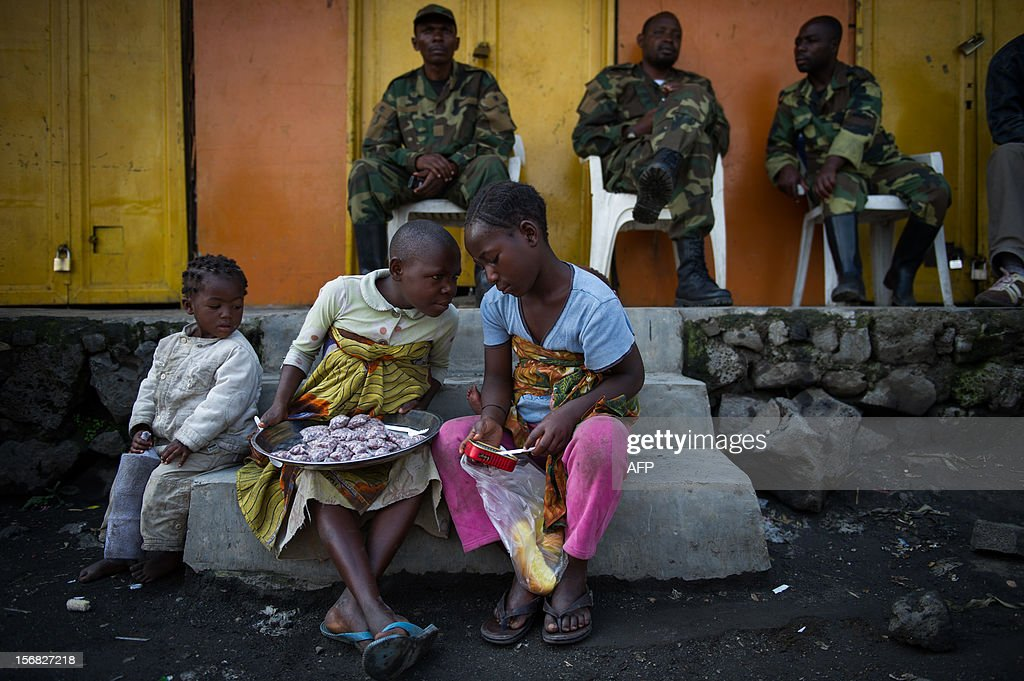 Congolese children sit on a step in Sake in front of a group of M23 rebels who controlled the eastern Democratic Republic of the Congo town November 22, 2012. Rebels took the town yesterday, but were engaged in heavy gunfights this afternoon as government-allied militia tried to retake it.