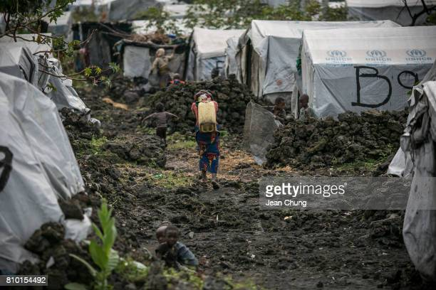 Congolese girl carries a water container in an IDP camp on June 7 2014 in Mugunga Democratic Republic of Congo Congolese in the North and South Kivu...