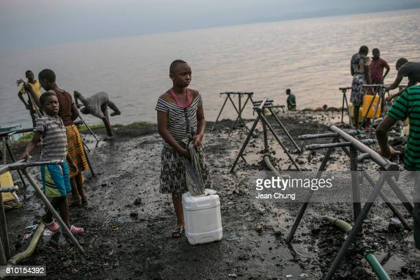 Congolese girl readies to carry a water container in which she fetched the water from the cityrun water stand next to the Kivu Lake on June 12 2014...