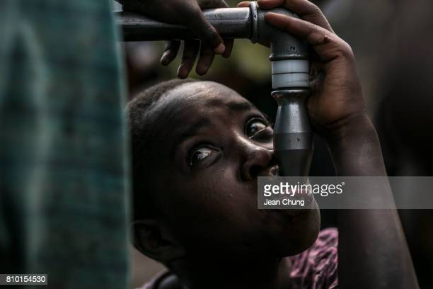 Congolese girl resorts to a few drops of water from a water stand inside Mugunga I IDP camp where the water supply had stopped from the morning until...