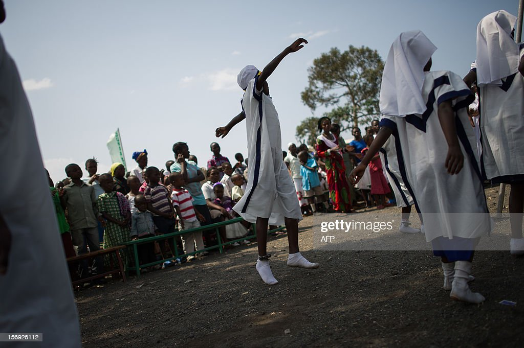 Congolese girls dance during a communion service at an open-air church service where thousands of internally displaced persons are sheltering on the outskirts of Goma in the east of the Democratic Republic of the Congo on November 25, 2012. Over half a million people have been displaced in eastern Congo since the outbreak of the M23 rebellion. Diplomatic efforts continued on November 25 to resolve the crisis in eastern DR Congo, with an M23 rebel leader expected to hold further talks with President Joseph Kabila as the African Union called on the rebels to pull out from Goma. AFP PHOTO / PHIL MOORE
