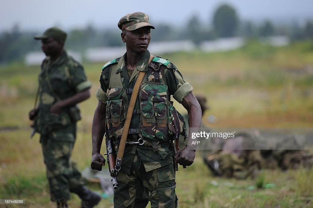 A Congolese government army (FARDC) soldier flexes at a military base in Sake, 26km from Goma in the east of the Democratic Republic of the Congo on December 3, 2012. FARDC Colonel Jean-Claude Yav from the Joint Verification Mechanism addressed Congolese troops this morning ahead of an expected move to Goma later today. AFP PHOTO/PHIL MOORE