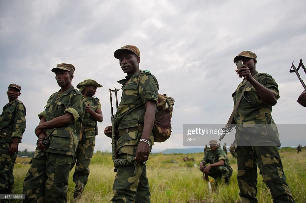 Congolese government army (FARDC) soldiers stand at a military base in Sake, 26km from Goma in the east of the Democratic Republic of the Congo on December 3, 2012. FARDC Colonel Jean-Claude Yav from the Joint Verification Mechanism addressed Congolese troops this morning ahead of an expected move to Goma later today. AFP PHOTO/PHIL MOORE