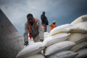 A Congolese man unloads sacks of food aid at the Mugunga III camp for internally displaced persons in the east of the Democratic Republic of the...