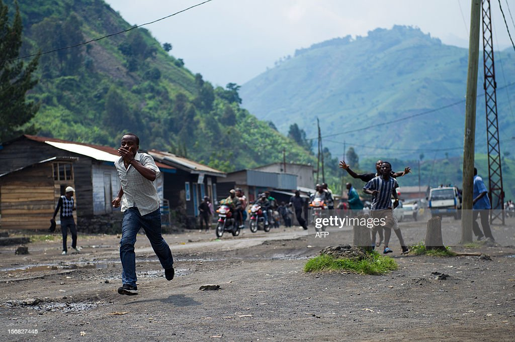 Congolese men run through the town of Sake, 26km from Goma, as gunfire erupted at the edge of the town in the east of the Democratic Republic of the Congo on November 22, 2012. Thousands fled the town today as gunfire and mortar explosions rocked the town, which was this morning under M23 rebel control.