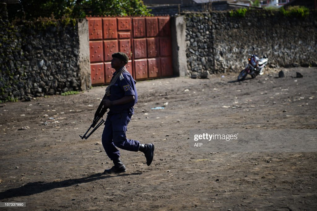A Congolese national police officer runs with a machine gun in the city of Goma, in the east of the Democratic Republic of Congo, on December 2, 2012. M23 rebels pulled out of Goma yesterday, leaving the United Nations and the police in the city, many of whom had deserted to M23 when it fell to rebel control. AFP PHOTO / PHIL MOORE