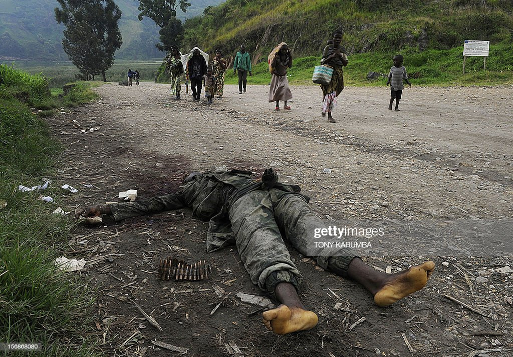 Congolese people carrying their belongings walk past the body of a government soldier killed during clashes with M23 rebels overnight as they flee on...