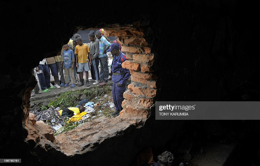 Congolese police officer is seen through a hole on the wall of a cell at Muzenze prison on November 21, 2012 in Goma. Almost all inmates of Goma's main prison managed to break out after prison warders abandoned their positions to flee from advancing M23 rebels two days ago. The M23 rebel group in the Democratic Republic of Congo, which says it now controls all of Goma and nearby crossing points on the border with Rwanda vowed today it would not stop at Goma, after seizing the key eastern city this week. A spokesman for the M23 rebel group in the Democratic Republic of Congo called Wednesday for President Joseph Kabila to step down, saying he was not the legitimate winner of elections last year. AFP PHOTO/Tony KARUMBA