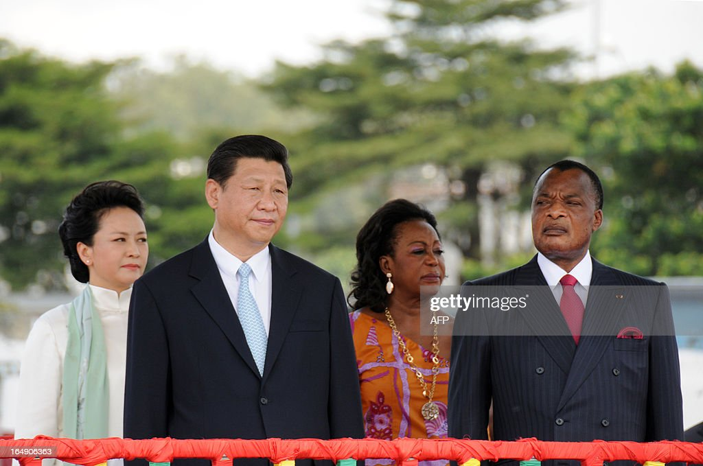 Congolese President Denis Sassou Nguesso (R) and his wife Antoinette (2nd R) welcome China's new President Xi Jinping (2nd L) and and his wife Peng Liyuan (L) on March 29, 2013 upon their arrival at Brazzaville's Maya-Maya airport on the final leg of a three-nation Africa tour that has underscored Beijing's growing presence in the resource-rich continent. Deals worth several billion dollars are due to be signed during Xi's two-day visit to Congo, the first by a Chinese president to the impoverished country of four million with significant oil resources. AFP PHOTO / Laudes Martial Mbon