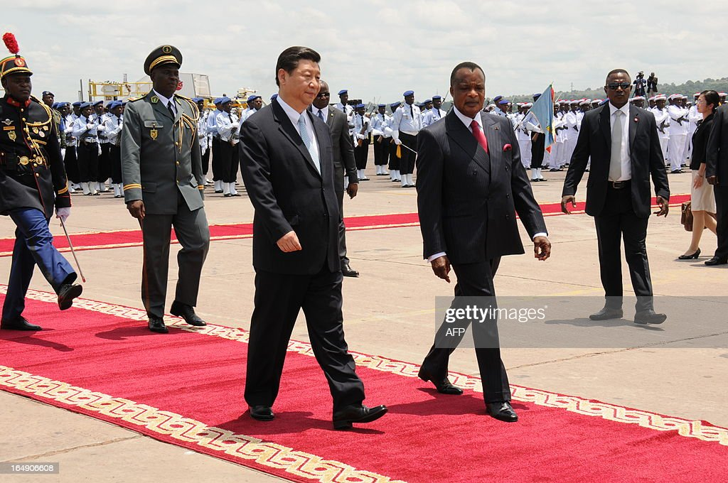 Congolese President Denis Sassou Nguesso (R) welcomes China's new President Xi Jinping (L) on March 29, 2013 upon their arrival at Brazzaville's Maya-Maya airport on the final leg of a three-nation Africa tour that has underscored Beijing's growing presence in the resource-rich continent. Deals worth several billion dollars are due to be signed during Xi's two-day visit to Congo, the first by a Chinese president to the impoverished country of four million with significant oil resources. AFP PHOTO / Laudes Martial Mbon