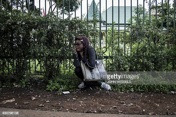 Congolese protester hides after police opened fire with rubber bullets and stun grenades during a protest outside the Democratic Republic of the...