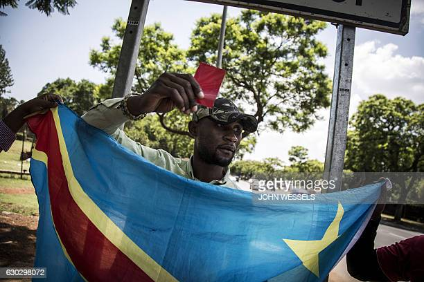 A Congolese protester holds up a red card in defiance against the President of the Democratic Republic of the Congo Joseph Kabila at a protest...