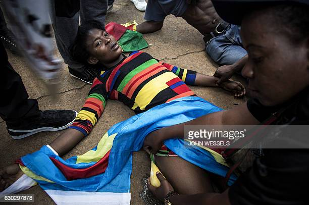 Congolese protester lies on the ground after police opened fire wth rubber bullets whilst they protest outside the Democratic Republic of the Congo's...