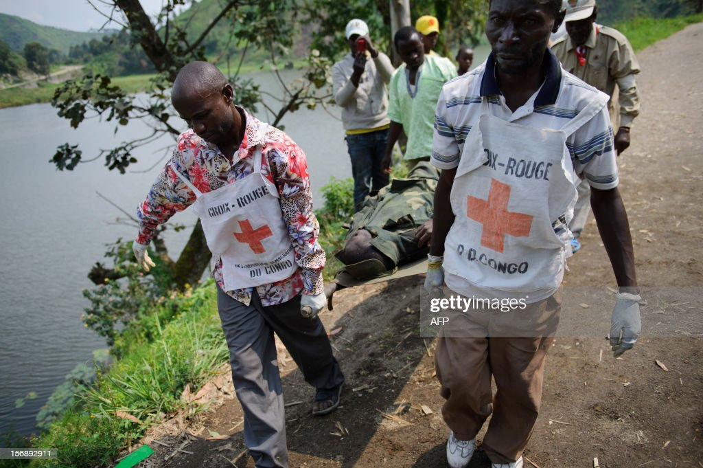 Congolese Red Cross volunteers carry the corpse of a government army soldier left lying on the roadside near Sake in the east of the Democratic Republic of the Congo on November 24, 2012. The Red Cross were working around Sake today, clearing the bodies left from fighting on Thursday as M23 rebels clashed with the government army. AFP PHOTO/PHIL MOORE