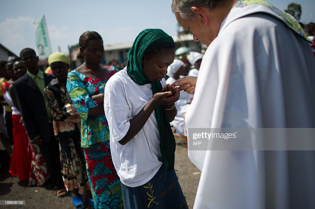 A Congolese woman takes communion at an open-air church service where thousands of internally displaced persons are sheltering on the outskirts of Goma in the east of the Democratic Republic of the Congo on November 25, 2012. Over half a million people have been displaced in eastern Congo since the outbreak of the M23 rebellion. Diplomatic efforts continued on November 25 to resolve the crisis in eastern DR Congo, with an M23 rebel leader expected to hold further talks with President Joseph Kabila as the African Union called on the rebels to pull out from Goma.