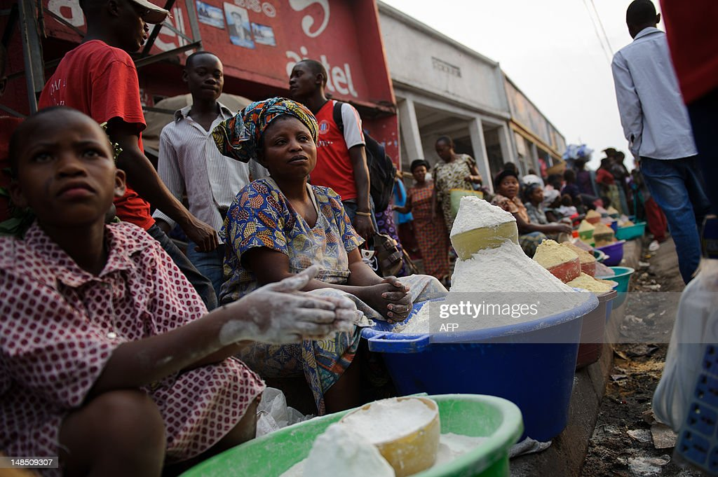 Congolese women and girls sell manioc flour on the side of a pavement in the market district of Goma in the east of the Democratic Republic of the Congo on July 18, 2012. 'Fufu', a dish made by mixing the flour with water, forms a staple of the Congolese diet.