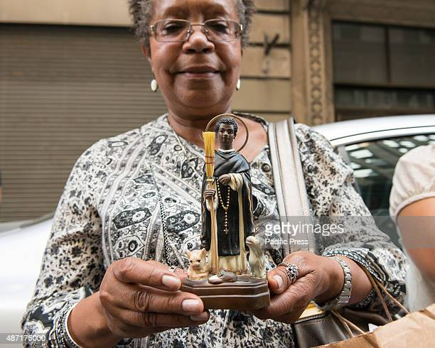 A congregant holds a miniature sculpture of St Martin de Porres complete with his two iconic features a broom and a trio of cat dog and mouse The...