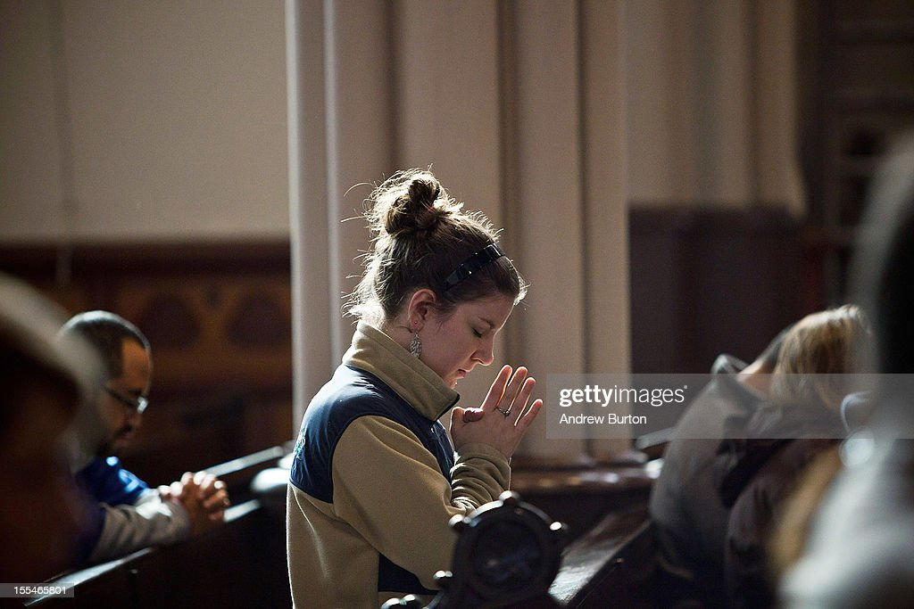 A congregant of Our Lady of Grace church prays during mass on November 4, 2012 in Hoboken, New Jersey. Areas affected by Superstorm Sandy, including Hoboken, are attempting to return to normal, but a lack of water and electricity, as well as cold weather, continueto plague much of the area.