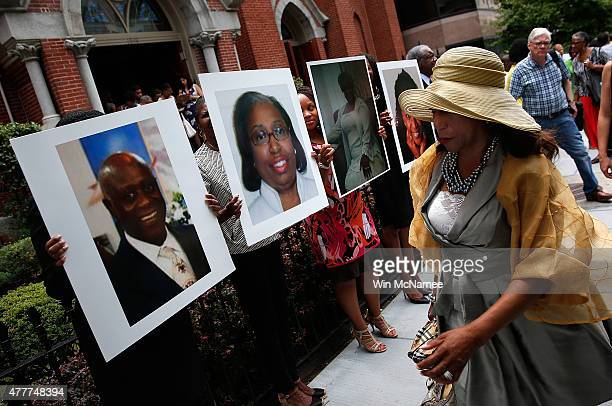 Congregants depart a prayer vigil for the nine victims killed at the Emanuel African Methodist Episcopal Church pass by photographs of the nine...