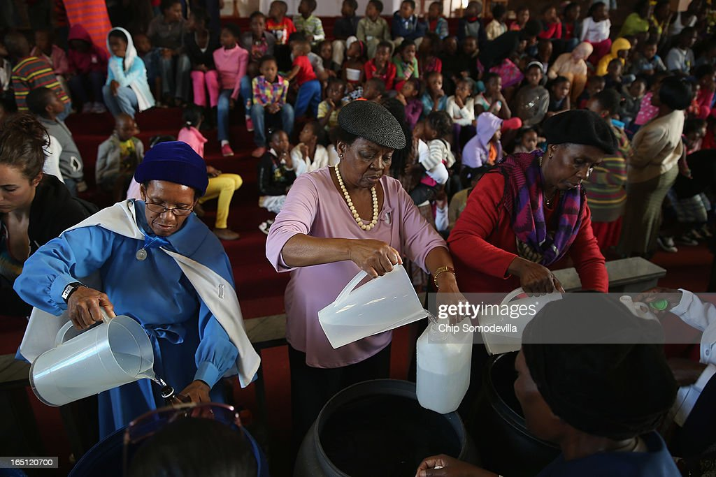 Congregants fill bottles with holy water after Easter services at Regina Mundi Catholic Church in the Soweto area March 31, 2013 in Johannesburg, South Africa. A central gathering place during he anti-apartheid struggle, the church held prayers for former South African President Nelson Mandela, 94, who is in the hospital for the third time since December with lung problems. Referring to Mandela by clan name, Madiba, President Jacob Zuma said, 'We appeal to the people of South Africa and the world to pray for our beloved Madiba and his family and to keep them in their thoughts.' Mandela's lungs were damaged when he contracted tuberculosis during his 27 years in the infamous Robben Island prison. Mandela became the nation's first democratically elected president in 1994 following the end of apartheid.