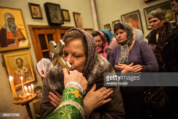 Congregants kiss a cross held by Father Alexandr Matveev at the end of a church service in the office space of Saint Johan Krondshtadsky Church on...